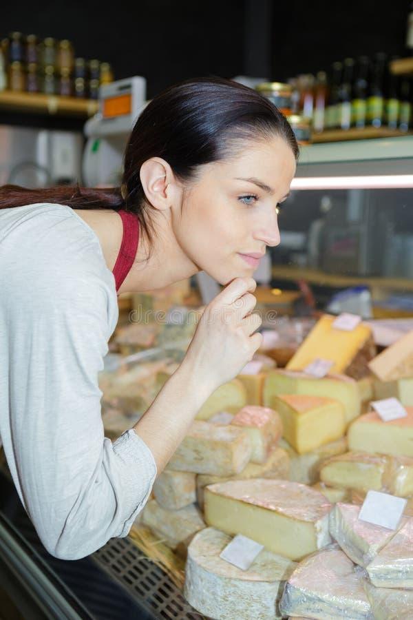 Morenita femenina feliz que vende el queso en la tienda foto de archivo libre de regalías