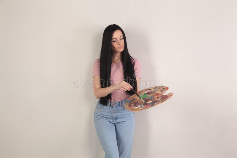 Morenita hermosa con las sonrisas largas del pelo que celebran una paleta de colores en sus manos, ella se coloca delante de un f foto de archivo