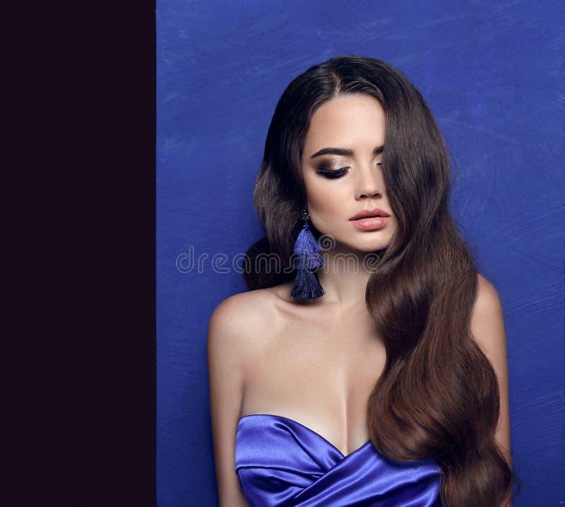 Morenita hermosa con los pendientes de la borla sobre azul Joya de la joyería fotos de archivo