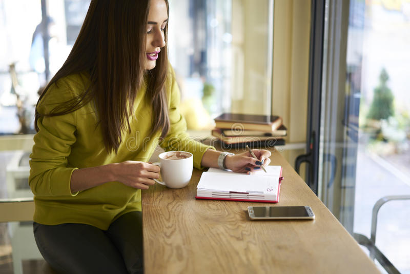 Morenita hermosa en un café de consumición de la blusa amarilla en rotura de trabajo usando Internet inalámbrico y smartphone fotos de archivo libres de regalías