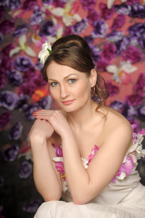 Morenita hermosa en un fondo de la flor imagenes de archivo
