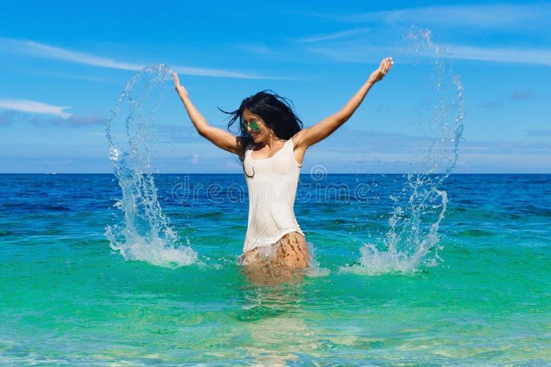 Morenita hermosa en una camiseta mojada que descansa sobre un mar tropical T fotografía de archivo libre de regalías