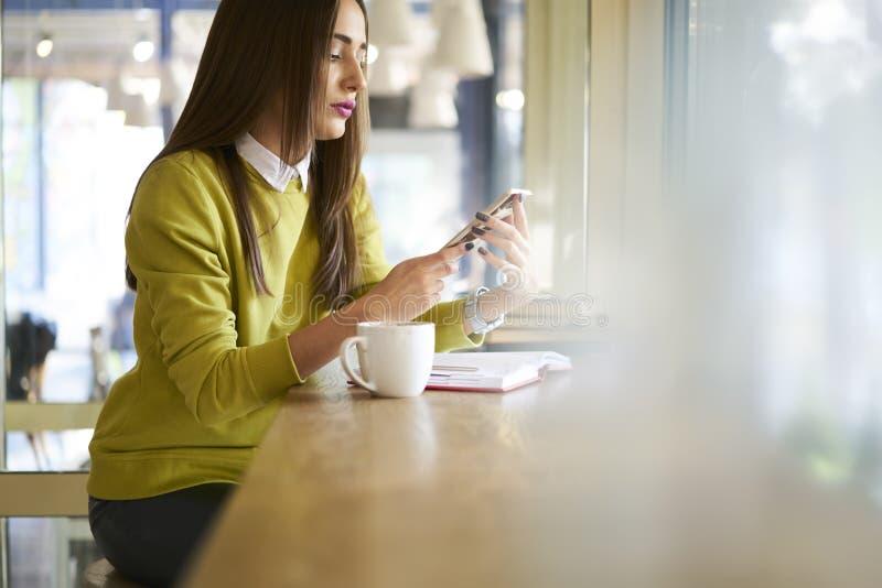 Morenita hermosa en una conexión inalámbrica amarilla del uso de la tienda de la blusa en el café y la PC portátil moderna que tr imagen de archivo
