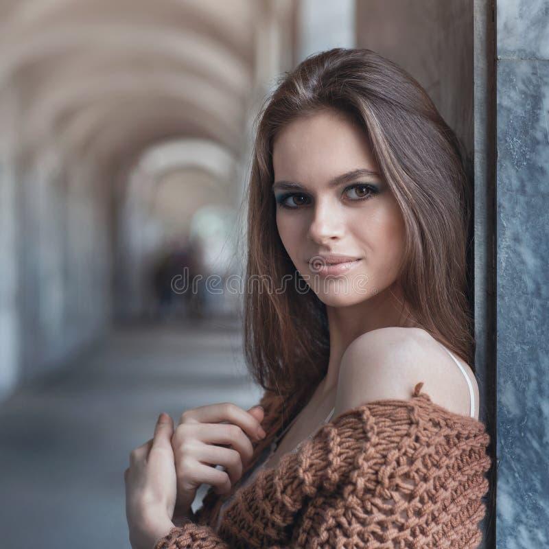 Morenita hermosa joven en ropa de moda cerca de la pared foto de archivo libre de regalías