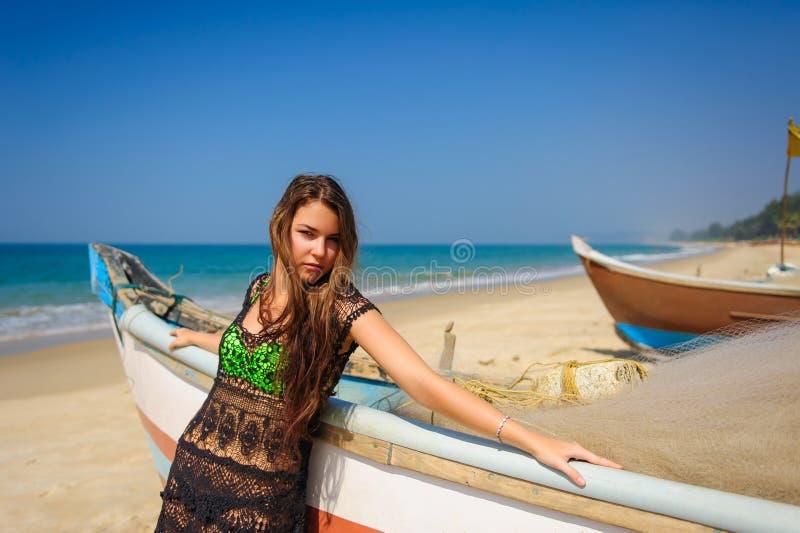 Morenita hermosa joven en vestido de la playa en el mar azul cerca del barco de pesca de madera Relajación tropical del verano al imagenes de archivo