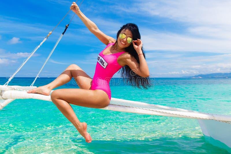 Morenita hermosa joven que se divierte en una playa tropical en el s imagen de archivo