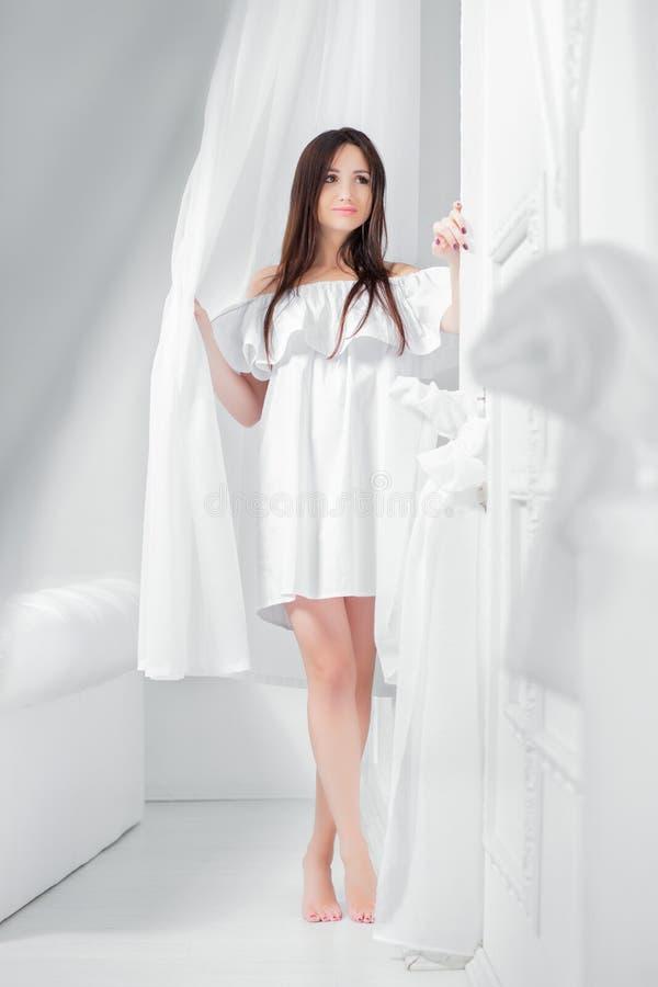 Morenita hermosa joven vestida en un vestido blanco imagen de archivo