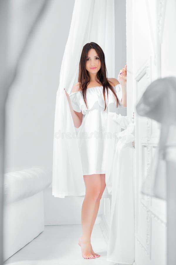 Morenita hermosa joven vestida en un vestido blanco fotos de archivo
