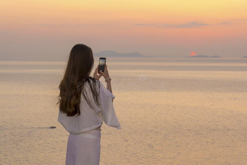 Morenita hermosa que toma las imágenes de la puesta del sol en Santorini La muchacha en vestido blanco transparente hace la fotog imágenes de archivo libres de regalías