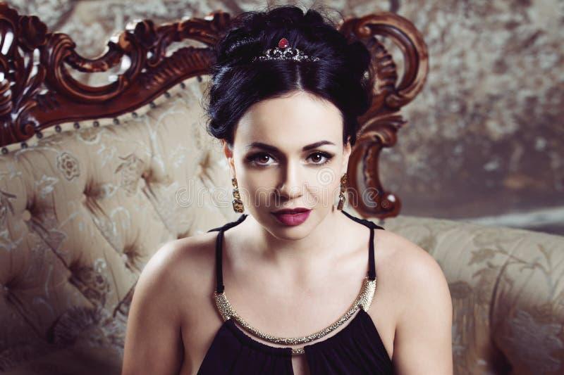 Morenita joven atractiva que se sienta en el sofá hermoso, primer del retrato, sombreador de ojos del oro fotos de archivo libres de regalías