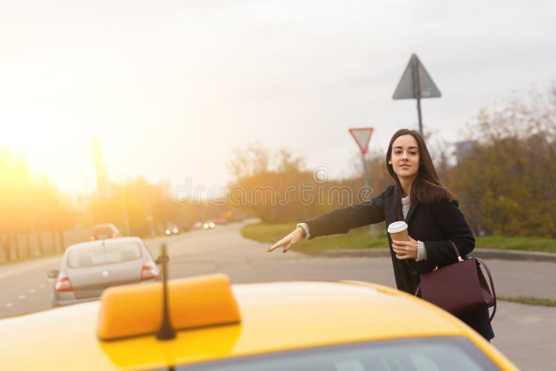 Morenita joven con el bolso de Borgoña que excava el taxi amarillo foto de archivo
