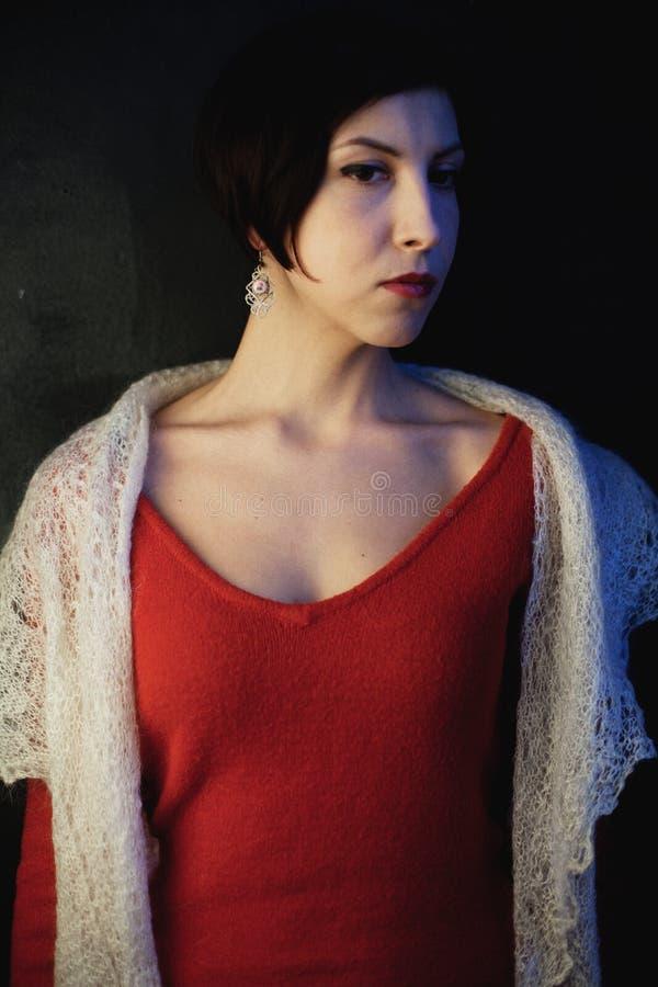 Morenita joven con un corte de pelo corto en un vestido rojo y un mantón suave foto de archivo libre de regalías