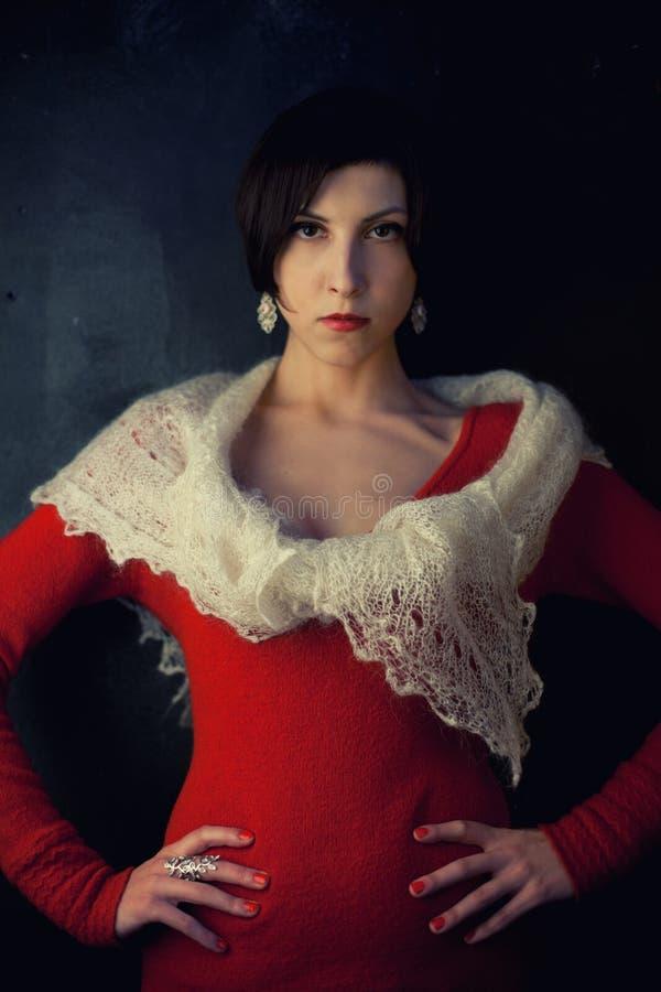 Morenita joven con un corte de pelo corto en un vestido rojo y un mantón suave fotos de archivo