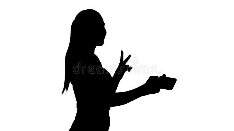 Morenita joven de la silueta que toma la foto del selfie en la sonrisa del smartphone alegre y caminar fotos de archivo libres de regalías