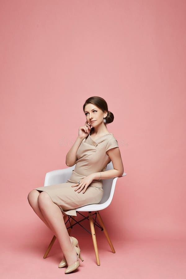 Morenita joven de moda y hermosa que se sienta en una silla con una cara pensativa imagen de archivo