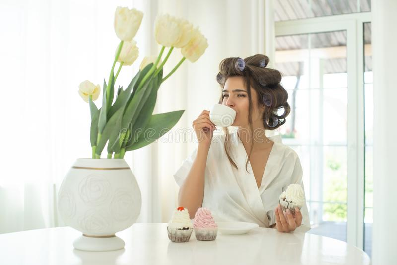 Morenita joven hermosa en los bigudíes de pelo que gozan del café y que comen las magdalenas para el desayuno por la mañana en br foto de archivo libre de regalías
