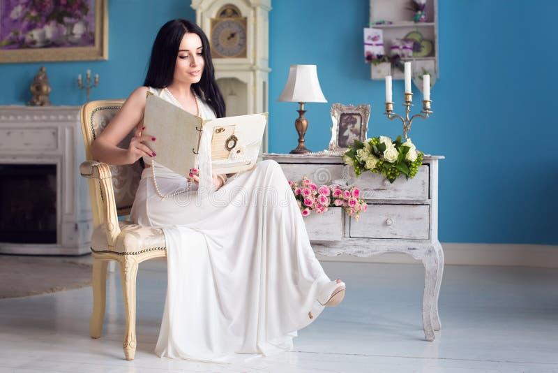 Morenita joven hermosa en un vestido blanco largo y un collar de fotografía de archivo libre de regalías