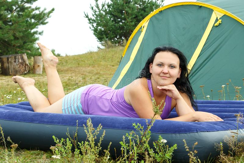 Morenita joven que descansa sobre un colchón inflable en la tienda en la hierba verde imágenes de archivo libres de regalías