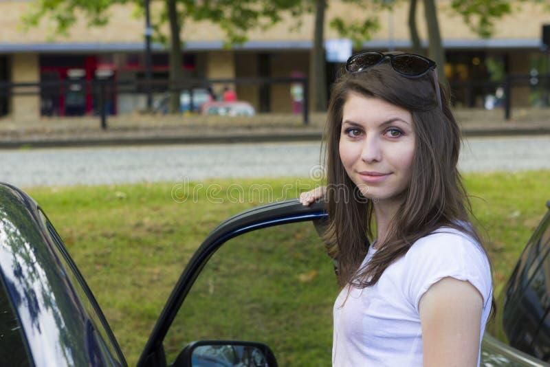 Morenita joven que presenta cerca del coche fotos de archivo
