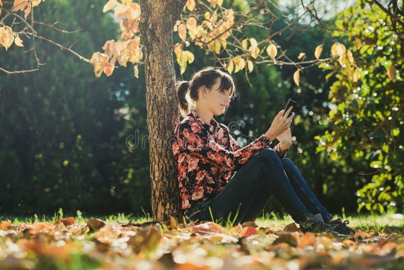 Morenita joven usando su teléfono que se sienta debajo de un árbol fotografía de archivo libre de regalías