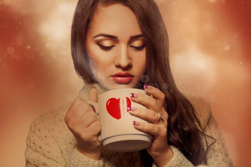 Morenita joven voluptuosa con la bebida caliente en taza fotos de archivo libres de regalías