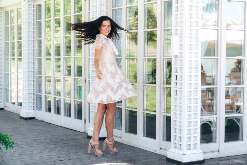 Morenita juguetona con las piernas largas hermosas que presentan en vestido beige del color afuera cerca de una pared de madera y imágenes de archivo libres de regalías