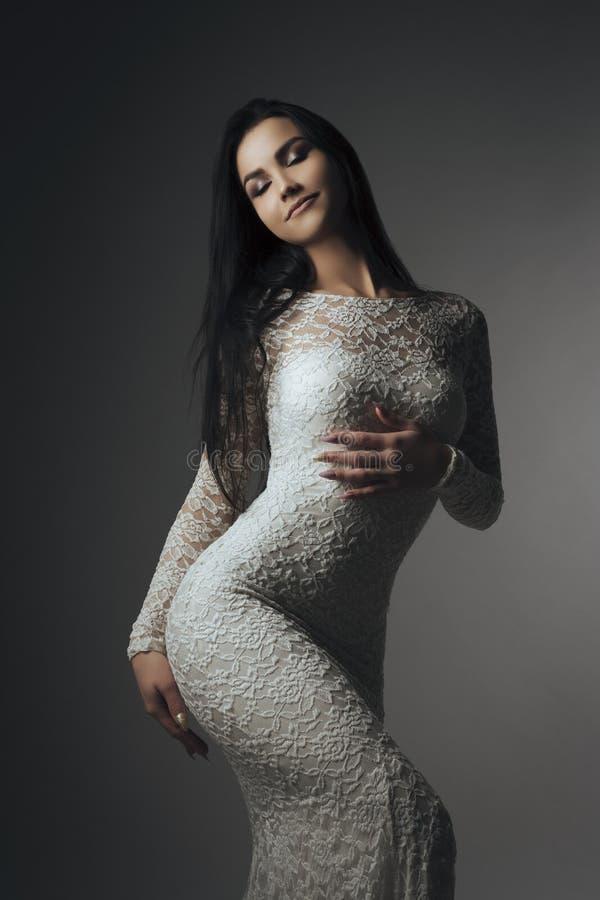 Morenita magnífica en vestido del cordón contra la pared gris foto de archivo