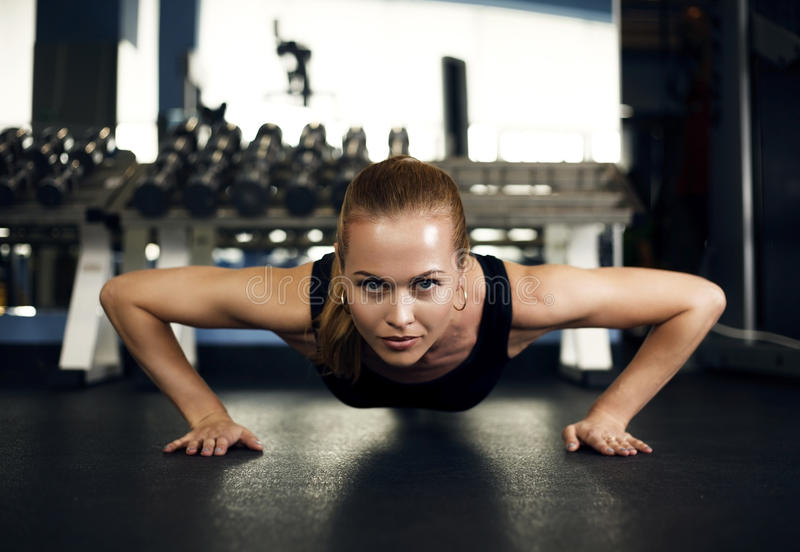 Morenita magnífica que calienta y que hace algunos pectorales en el gimnasio foto de archivo