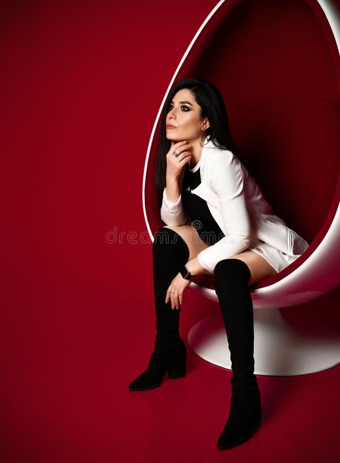 Morenita pensativa atractiva elegante de la mujer en ropa blanco y negro y altas botas que se sientan en una silla oval moderna e fotos de archivo libres de regalías
