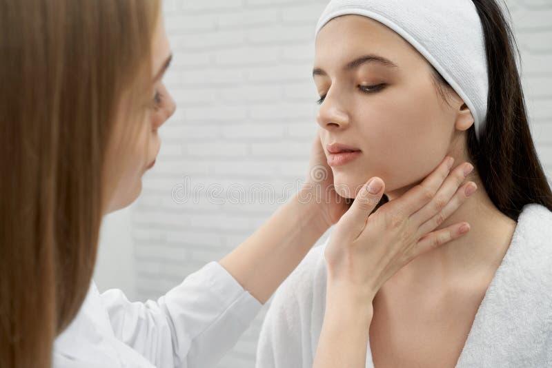 Morenita que mira abajo mientras que piel de examen del doctor de sexo femenino imagen de archivo