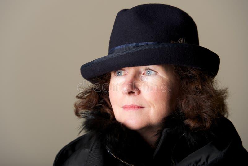 Morenita que mira fijamente en sombrero flexible y capa negros foto de archivo libre de regalías