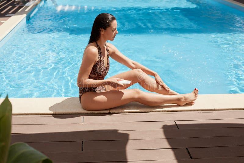 Morenita relajada deportiva que se sienta cerca de piscina en piso de madera, aplicándose tomando el sol la crema cuidadosamente, fotos de archivo