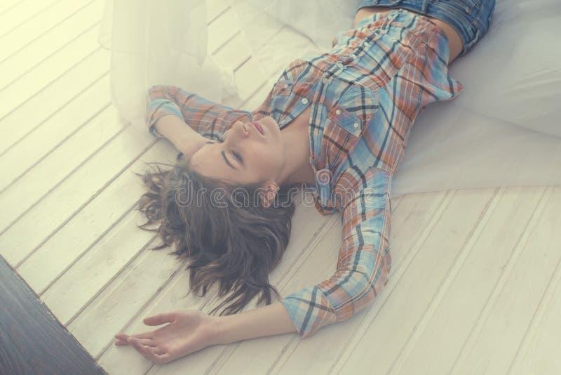 Morenita romántica hermosa de la mujer/de la muchacha que miente en la cama en su sitio en casa Camisa sport vestida, luz de Sun, foto de archivo libre de regalías