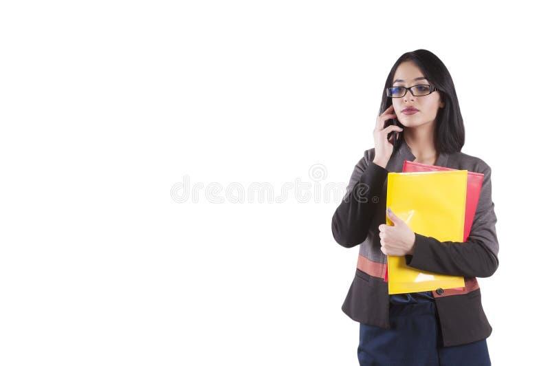 Morenita seria aislada con el teléfono, conversación, vidrios, carpeta de la empresaria joven fotos de archivo libres de regalías