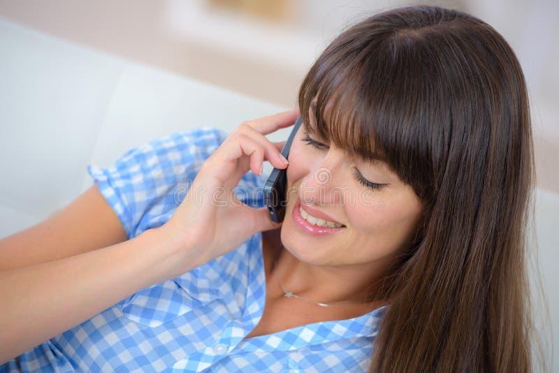 Morenita sonriente en llamada de teléfono en sala de estar fotos de archivo libres de regalías