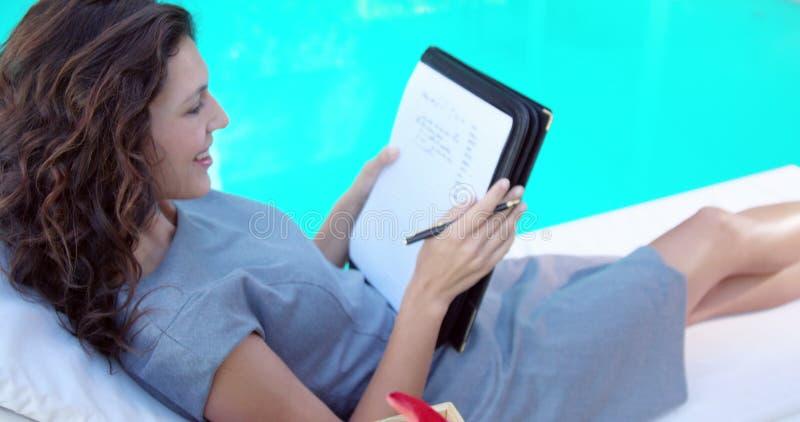 Morenita sonriente que mira una lista metrajes