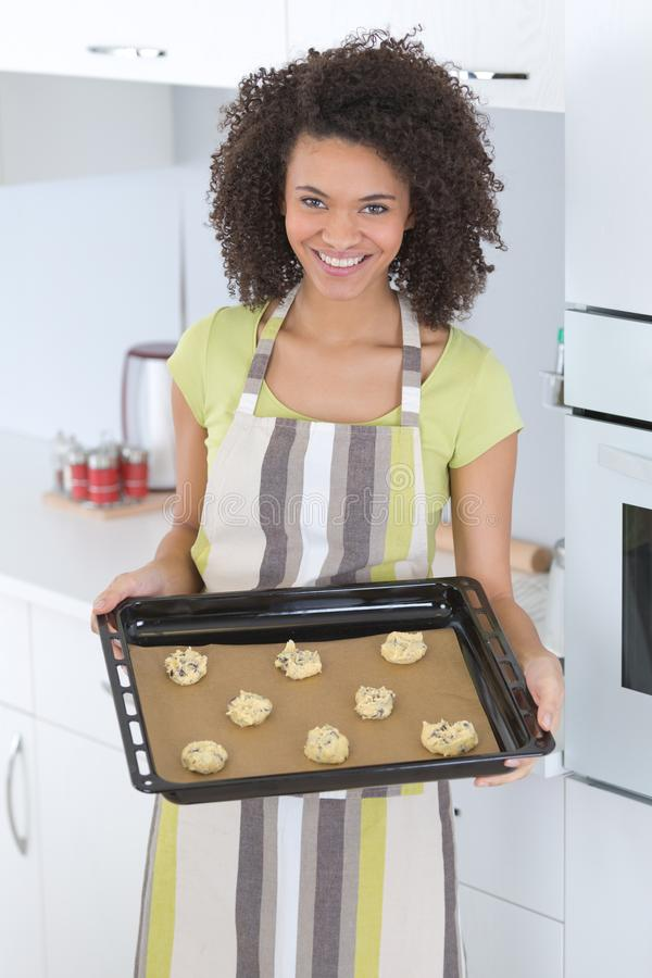 Morenita sonriente que muestra las galletas en la lata de hornada en casa imagen de archivo