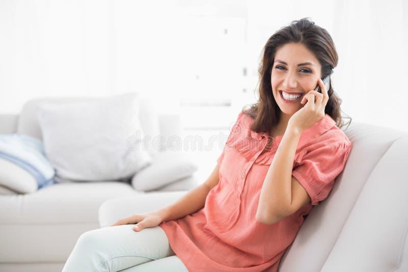 Morenita Sonriente Que Se Sienta En Su Sofá En El Teléfono Imagenes de archivo
