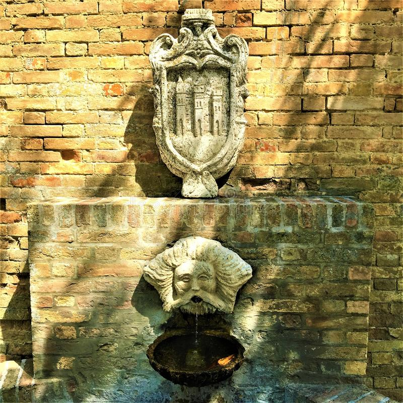 Moresco town in Fermo province, Marche region, Italy. Fountain, masque and symbol. Moresco town in Fermo province, Marche region, Italy. Medieval atmosphere stock photography