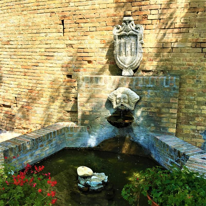 Moresco town in Fermo province, Marche region, Italy. Fountain, masque and symbol. Moresco town in Fermo province, Marche region, Italy. Medieval atmosphere stock image