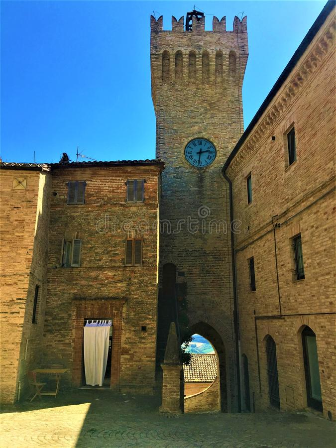 Moresco town in Fermo province, Marche region, Italy. Medieval tower, clock, white curtain and arch. Moresco town in Fermo province, Marche region, Italy royalty free stock photo