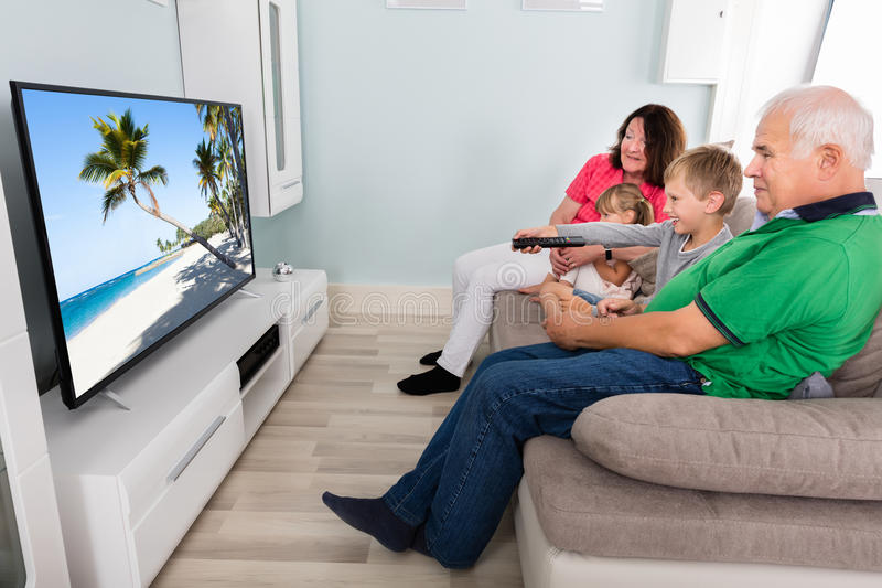 Morförälder och barnbarn som tillsammans håller ögonen på television arkivbild
