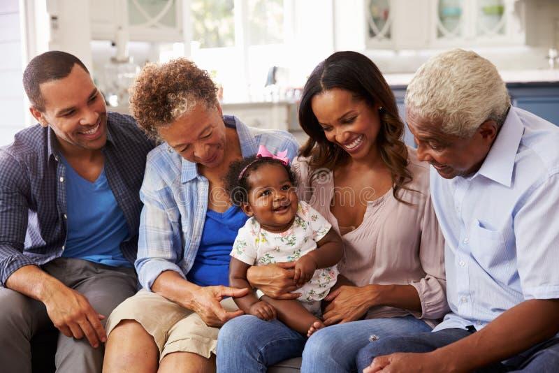Morföräldrar, föräldrar och ett lyckligt behandla som ett barn flickan på knä för mumï¿ ½ s royaltyfria bilder