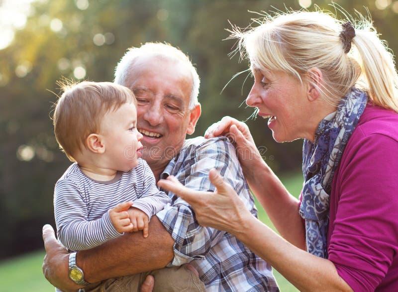 Morföräldrar med att spela för sonson royaltyfri fotografi