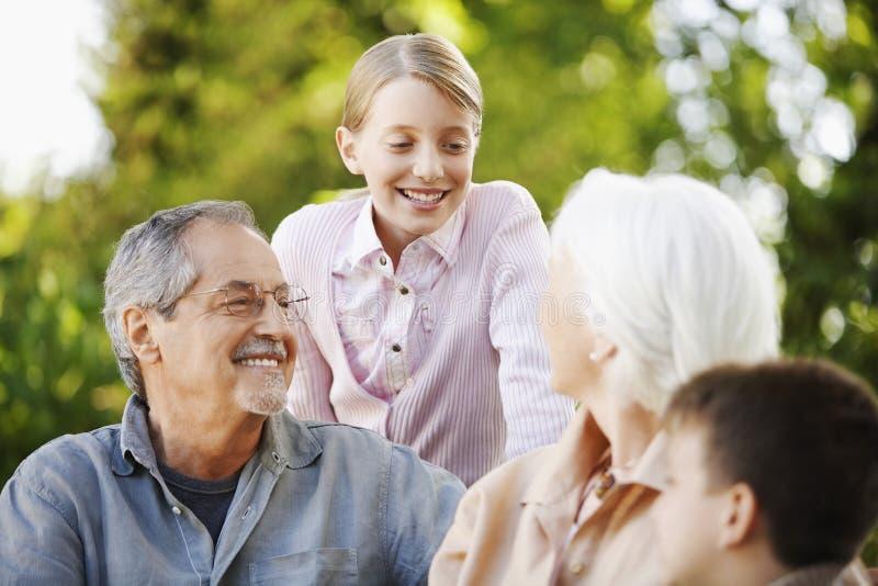 Morföräldrar med barnbarn i trädgård arkivbild