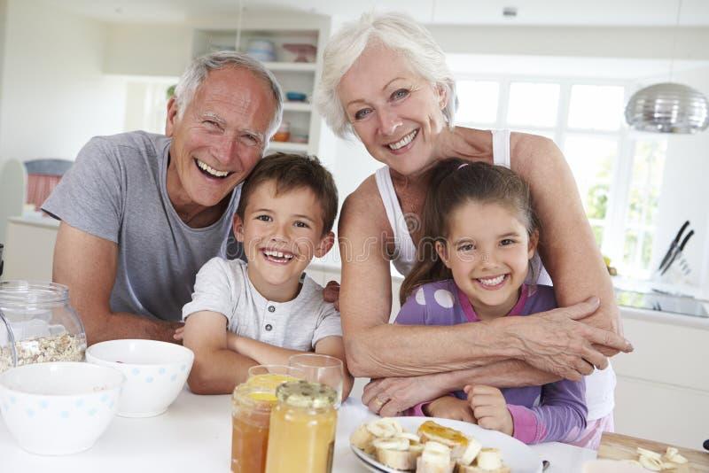 Morföräldrar med barnbarn som äter frukosten i kök royaltyfri fotografi