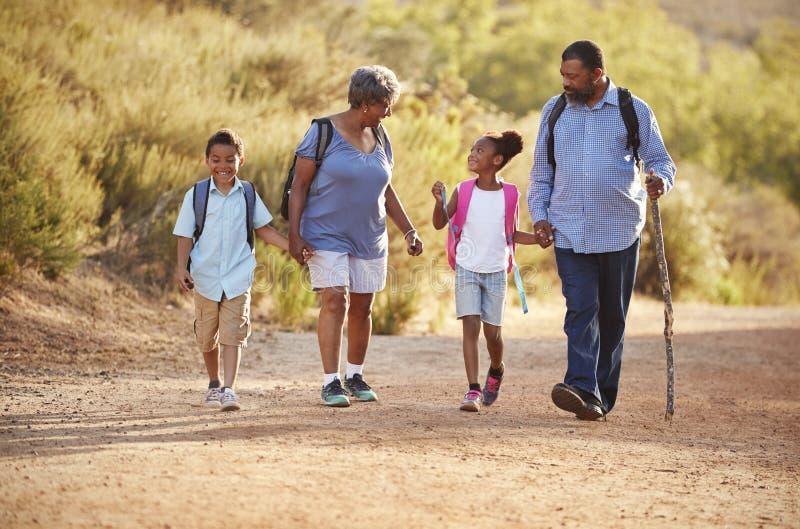 Morföräldrar med barnbarn som bär ryggsäckar som tillsammans fotvandrar i bygd fotografering för bildbyråer