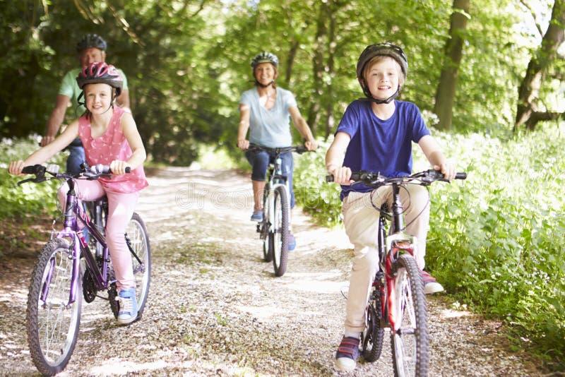 Morföräldrar med barnbarn som cyklar i bygd arkivbilder