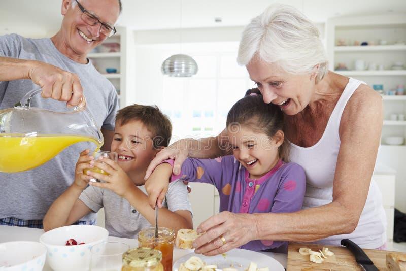 Morföräldrar med barnbarn som gör frukosten i kök royaltyfria foton