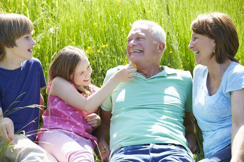 Morföräldrar med barnbarn som tillsammans kopplar av i fält royaltyfri foto
